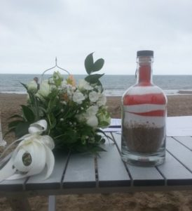 Mark and Kim chose orange and white sand for their sand pouring ceremony to match the theme of their beach wedding