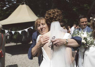 Bride and celebrant exchange a hug