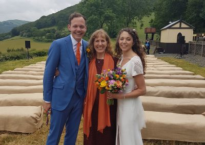 Bride and groom stand with celebrant by the Vale of Rheidol railway.