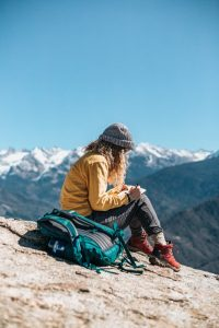 Girl sitting on a mountain writing