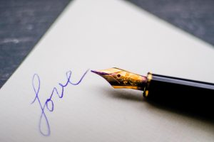 The inkpen writes the word Love