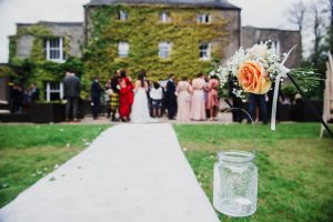 Wedding guests gather in front of the big house