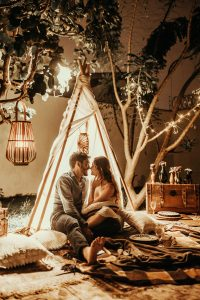 Two people sit in a tipi with a picnic