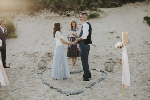 Bride and groom hold hands in a stone heart on the beach